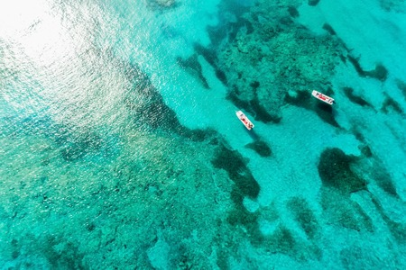 Foto de Top view of clear ocean water with reefs and boats. Nature summer background with sunshine - Imagen libre de derechos