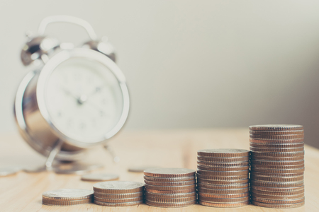 Photo for Stack of coins placed on stairs on wooden board with clock, Finance and investment have increased in value over time concept - Royalty Free Image