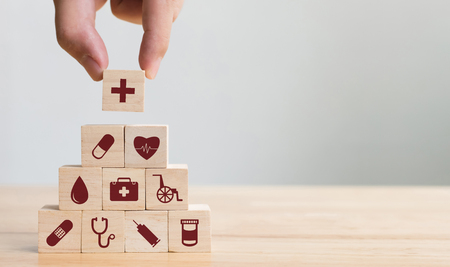 Foto de Hand arranging wood block stacking with icon healthcare medical, Insurance for your health concept - Imagen libre de derechos