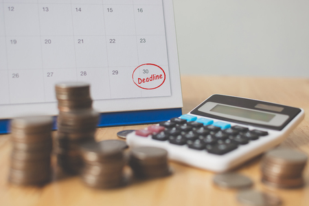 Foto de Tax payment season and finance debt collection deadline concept. Money coins stack, calendar and calculator - Imagen libre de derechos