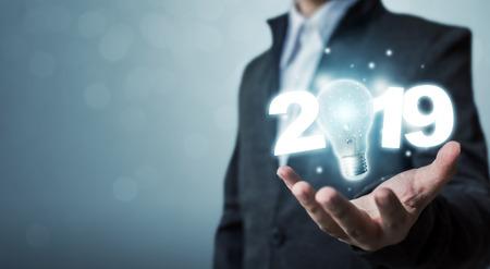 Photo pour Businessman hand holding light bulb with year 2019 idea innovation technology concept - image libre de droit