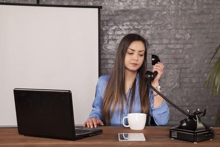 Photo pour business woman is negotiating with a landline phone - image libre de droit