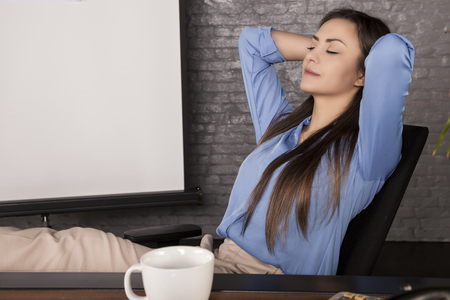 Foto de A young secretary enjoys a free moment, rest at work, close up - Imagen libre de derechos