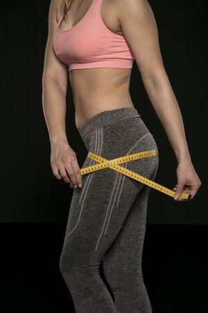 Foto de young woman with an athletic body uses a measuring tape - Imagen libre de derechos