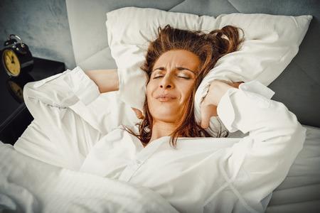 Photo pour Woman covering ears with pillow because of noise. - image libre de droit