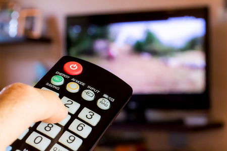 Foto de use the remote control to change channels on Television - Imagen libre de derechos