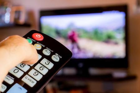 Foto de use the remote control to change channels on Television - Imagen libre de derechos