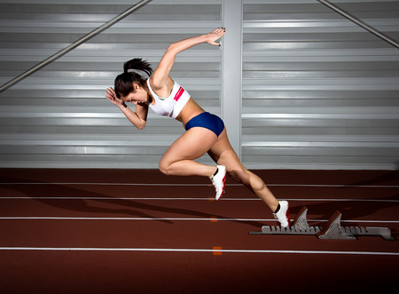 Photo pour Woman sprinter leaps from starting block. - image libre de droit