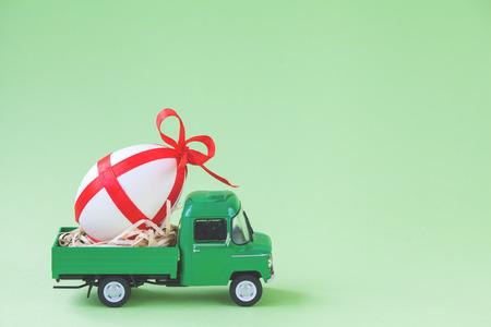 Foto de Green pickup toy carrying one decorated easter egg. - Imagen libre de derechos