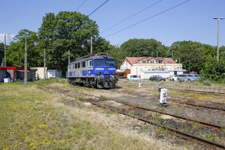 Foto per Kolobrzeg, Poland - June 18, 2019: The electric locomotive painted white and blue of PKP Intercity colors has been parked on a side-track, which is part of the railway station in the city. - Immagine Royalty Free