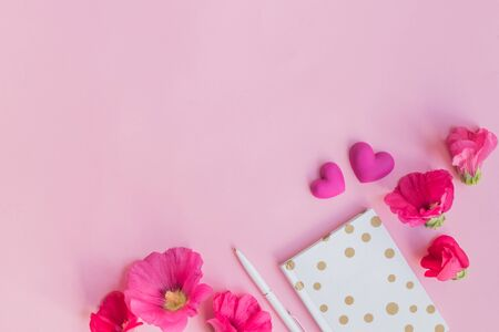 Photo for Flat lay desk with pink flowers and notebook on pink background - Royalty Free Image