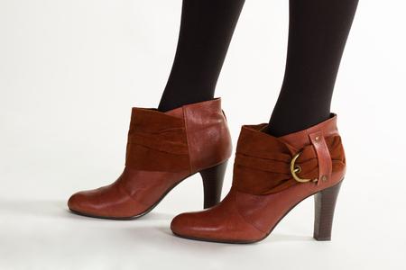 Foto de Brown leather ankle boot. Shoes with thin nubuck straps. Model in brown ankle boots. - Imagen libre de derechos