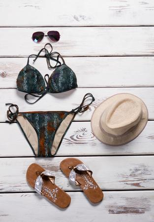 Photo for Dark swimsuit with flip flops. Brown flip flops and swimwear. Girl's beachwear on store showcase. Seasonal sale of stylish beachwear. - Royalty Free Image