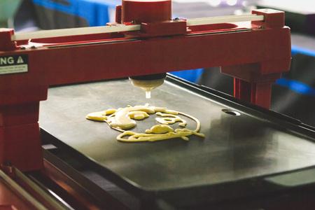 Foto de 3d printer for liquid test. 3D printer printing pancakes with liquid dough different shapes close-up. - Imagen libre de derechos