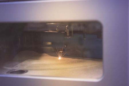 Foto de 3D printer printing metal. Laser sintering machine for metal. Metal is sintered under the action of laser into desired shape in working chamber. Modern additive technologies 4.0 industrial revolution - Imagen libre de derechos