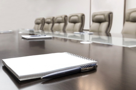 Photo for Closeup of notepad kept on table in empty conference room - Royalty Free Image