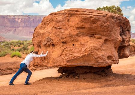 Foto de Girl pushing stone, impossible cocept - Imagen libre de derechos