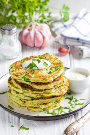 Foto de Zucchini pancakes with parsley and sour cream, summer food, delicious snack. High stack in a plate on white wood - Imagen libre de derechos