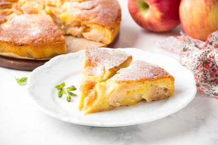 Foto de Apple pie with powdered sugar, classic Charlotte, biscuit dough. Golden brown, homemade food - Imagen libre de derechos