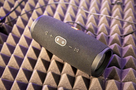 Foto de Moscow, Russia - October 04, 2019: close up of black portable bluetooth waterproof music speaker JBL Charge 4 rests on noise reduction cover. soft focus, background in blur - Imagen libre de derechos
