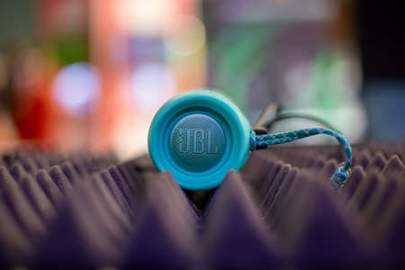 Foto de Moscow, Russia - October 04, 2019: Moscow, Russia - October 04, 2019: close up of blue portable bluetooth waterproof music speaker JBL Charge 4 rests on noise reduction cover. side view, soft focus, background in blur - Imagen libre de derechos