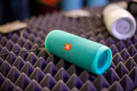 Foto de Moscow, Russia - October 04, 2019: close up of blue portable waterproof bluetooth music speaker JBL Charge 4 rests on noise reduction cover. soft focus, background in blur - Imagen libre de derechos