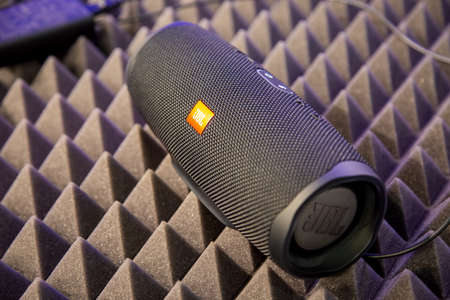 Foto de Moscow, Russia - October 04, 2019: close up of black portable bluetooth waterproof music speaker JBL Charge 4 rests on noise reduction cover. soft focus, background in blur. - Imagen libre de derechos
