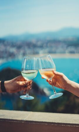 Photo pour Drink glasses white wine in friends hands outdoor sea nature holidays, two romantic couple toast with alcohol, happy people cheering fun vacation enjoying travel time together friendship love concept congratulations - image libre de droit