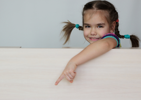 Photo pour Cute 5 years old girl with funny pigtails pointing with her fingers left down corner on white board, space for copy, advertising and announcement concept, studio shot over white background - image libre de droit