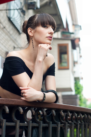 Photo pour Pretty slim young brunette woman model wearing black off-the-shoulder top, elegant earrings, beautiful hairstyle, leaning over the balustrade of a balcony, looking somewhere, dreaming and enjoying the day. - image libre de droit
