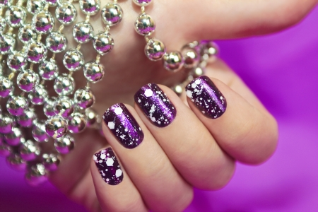 Snow manicure with the design of the white crumbs on violet brilliant varnish for the nails