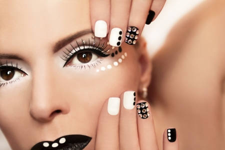 Makeup with rhinestones and manicure in black and white colors on the girl