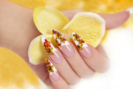 Nail with a pattern of yellow orchids on a long shaped nails