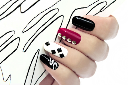 Photo pour Graphic manicure with black,Burgundy,white varnish and decorative ornaments on the nails  - image libre de droit
