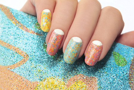 Foto de Pastel manicure with different colors of paint and coating in the form of colorful polosochku with stripes  - Imagen libre de derechos