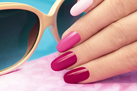 Photo pour    Pink manicure covered different in tone nail Polish on oval shaped nails  - image libre de droit