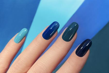 Foto de    Blue manicure in light and dark colors of lacquer on a striped background. - Imagen libre de derechos