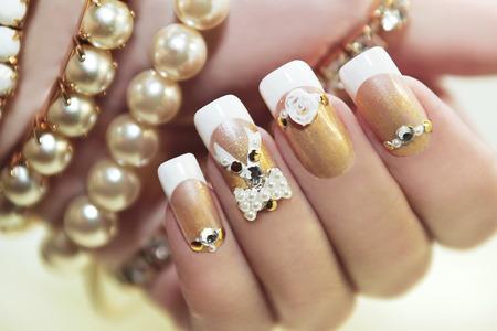 Foto de Pearl French manicure with rhinestones and embellishments. - Imagen libre de derechos