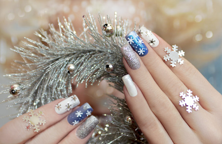 Manicure with snowflakes on your nails with colored lacquers on a rectangular shaped nails.