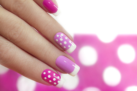 Photo pour Nail design with white dots on the French manicure with pink varnish of various shades. - image libre de droit