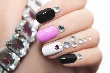 Foto de Colorful manicure oval shape nails with rhinestones. - Imagen libre de derechos