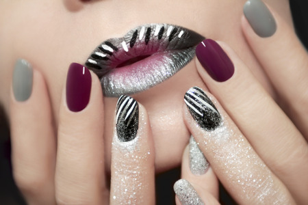 Foto de Design with white and black stripes on the lips and nails with glitter. - Imagen libre de derechos