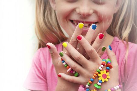 Foto de Children's multicolored manicure with ornaments on a hand. - Imagen libre de derechos