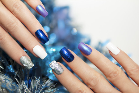 Photo pour Christmas blue and silver with white nail Polish manicure. - image libre de droit