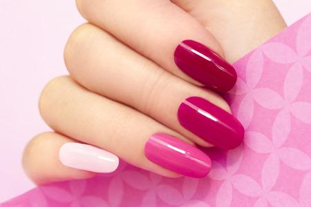 Foto de Multicolored manicure with different shades of pink nail Polish on women's hand - Imagen libre de derechos