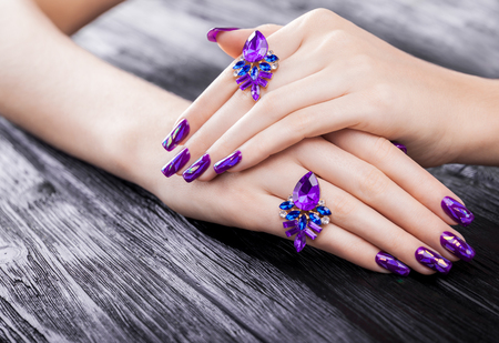 Photo pour Shattered glass purple manicure on black wooden background - image libre de droit
