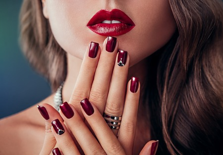 Photo for Beautiful woman with red lips and burgundy manicure - Royalty Free Image