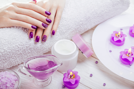 Photo for Beautiful purple manicure with spa essentials on wooden background - Royalty Free Image