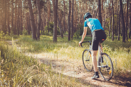 Young bicyclist riding in the forest