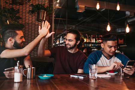 Photo for Happy arabian young man giving high five to his friend. Group of mixed race people having fun in lounge bar. Friends hangout and laughing - Royalty Free Image